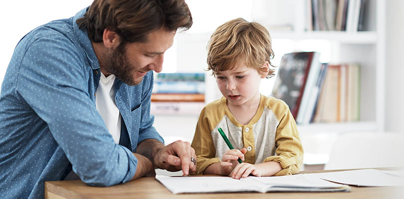 A father and son are working together on homework