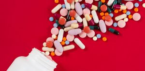 A pill bottle spilling various vitamin capsules