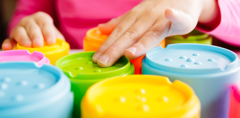 Little girl's hands touching cup toys with lifted markers